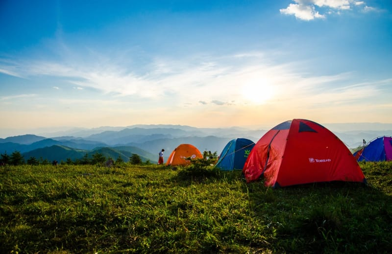 Dome camping tents and campers overlooking mountain ranges at sunrise