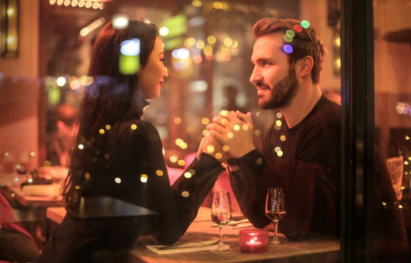 Boyfriend and girlfriend recreating their first date at a restaurant with the boyfriend about to propose to his girlfriend