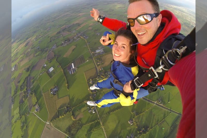 Man and woman in overalls skydiving over countryside
