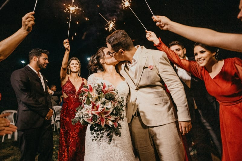 Married couple surrounded by wedding  party with sparklers