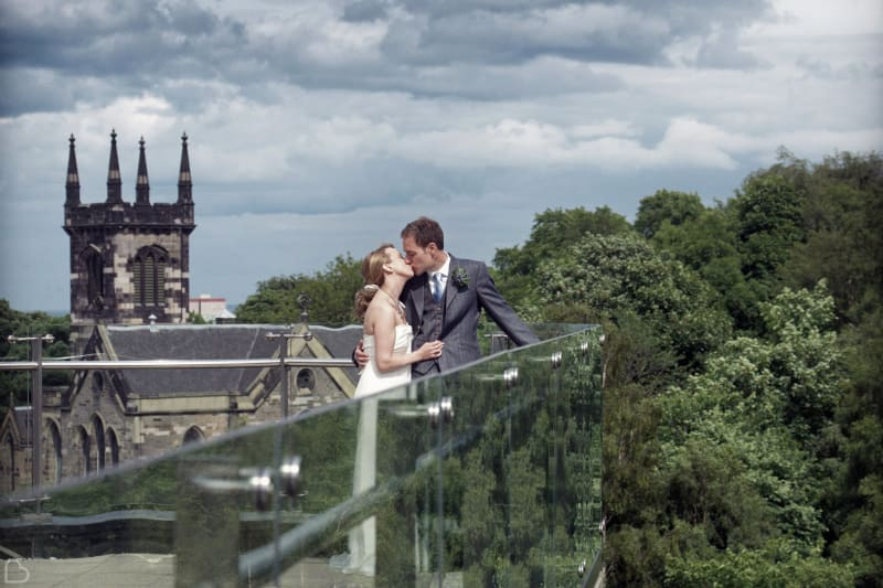 newlyweds kiss on the balcony of The Glasshouse Hotel.