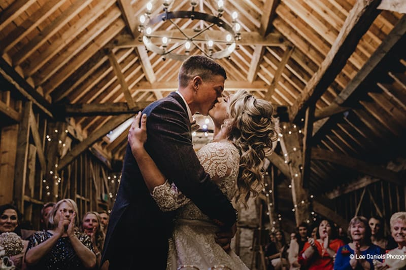 Newlyweds kiss at Bassmead Manor barns