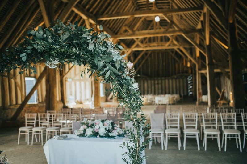 barn decorated for wedding ceremony with green arch.
