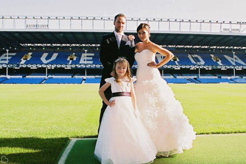 Couple and their daughter pose at the stadium