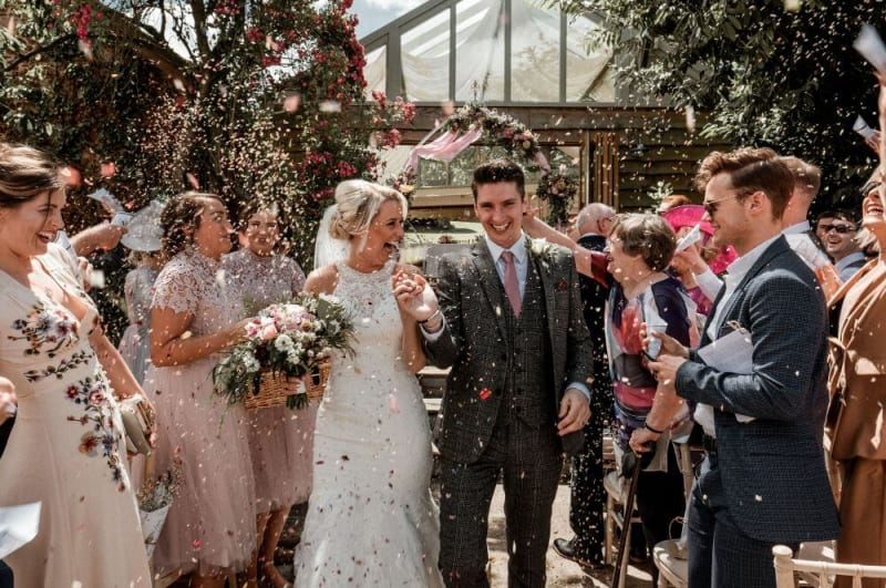 Newlywed couple exit the ceremony area whilst guests throw flower petals.