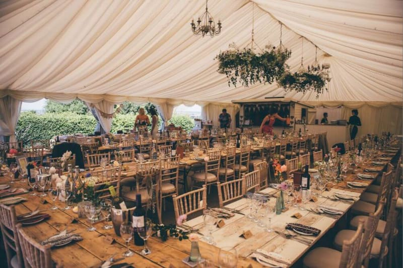 Inside of a white tent. Four long wooden tables are set for the dinner.