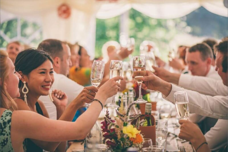 Guests holding champagne glasses and toasting.