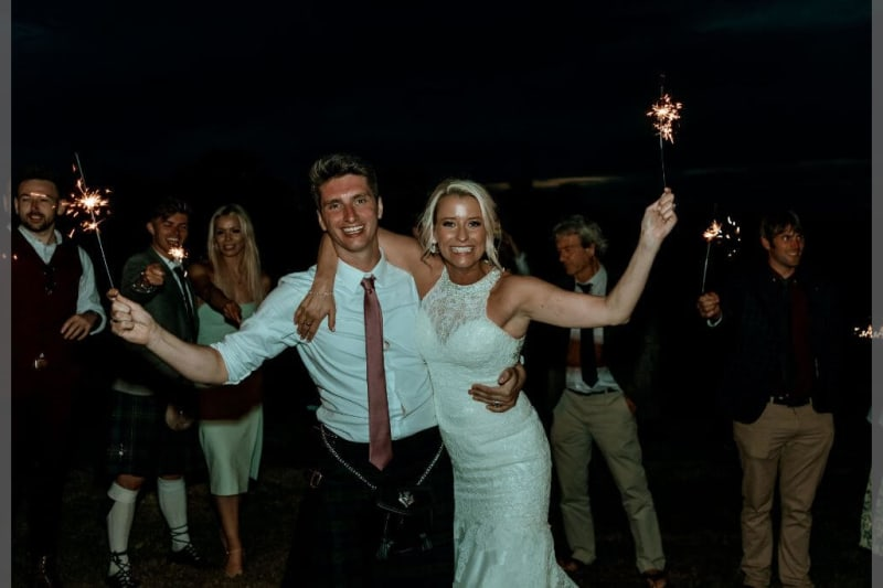 A newlywed couple hold sparkles while smiling.
