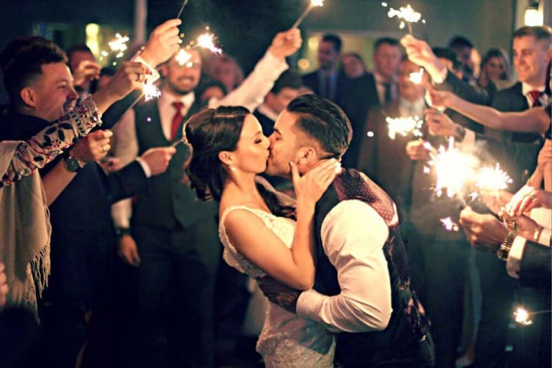 A couple is kissing while guests are holding lights around them.