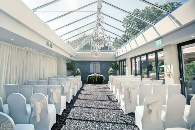 Inside the glass house. White chais are facing the ceremony area.