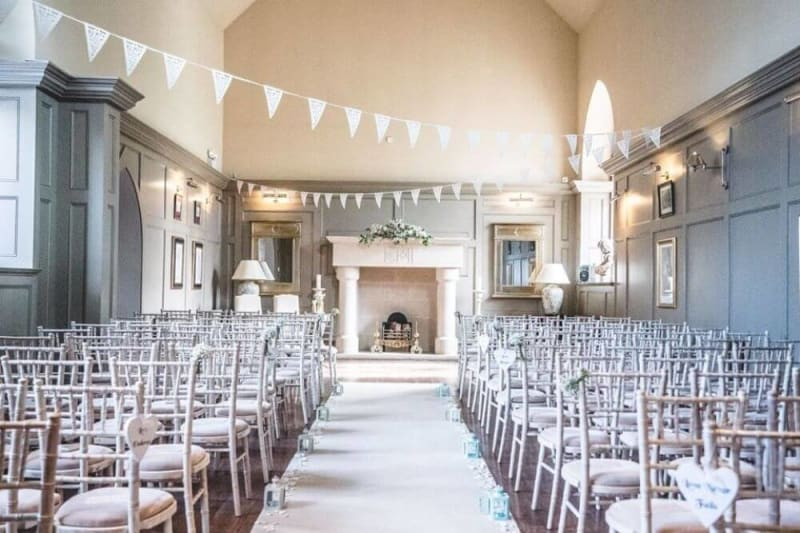 A white hall with a fireplace in the back. Several chais are lined up for a wedding.