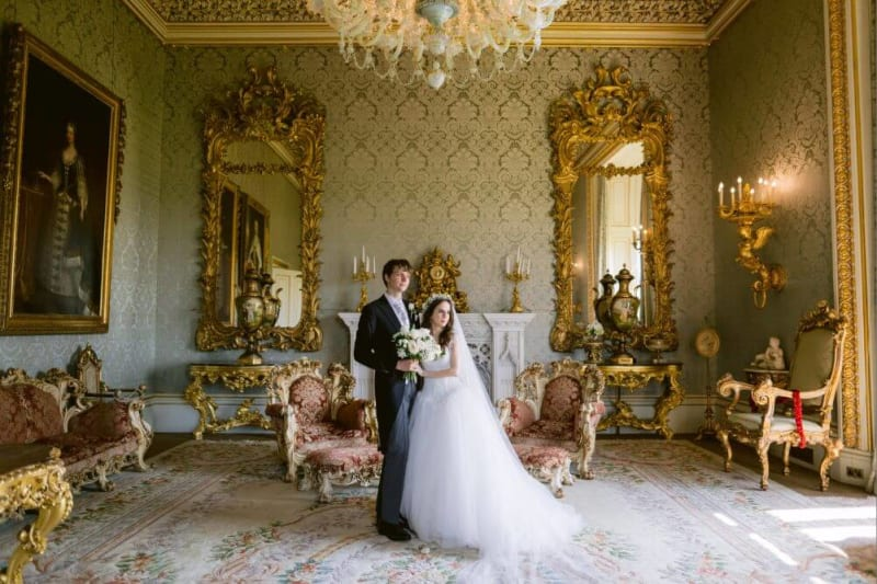 Bride and groom posing for a photo in an elegant room.