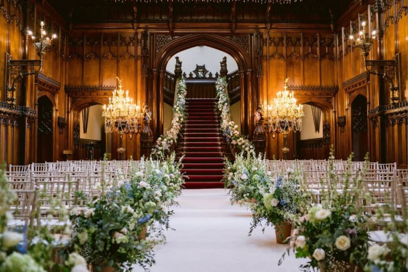 A grand inside staircase and chairs decorated with flowers for a wedding ceremony.