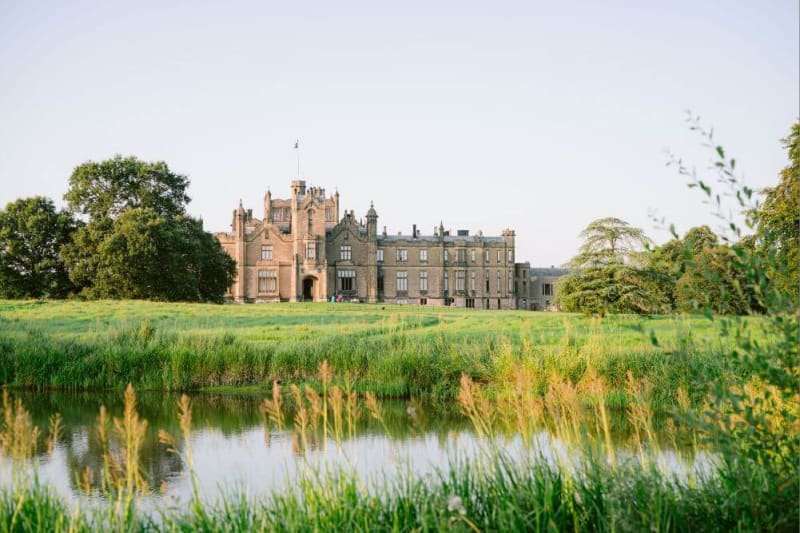 Outside photograph of a castle overlooking a lake.