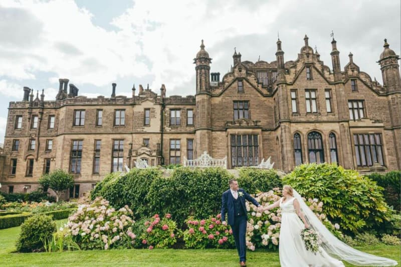 Bride and groom hold hands in a garden outside a castle.