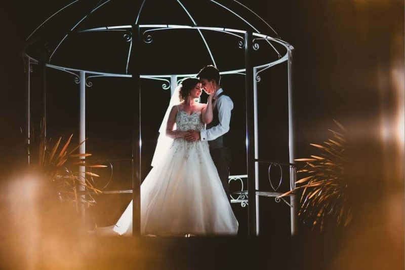 At night, a couple embraces under the wedding gazebo.