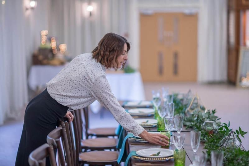 A woman sets the table for the wedding feast.