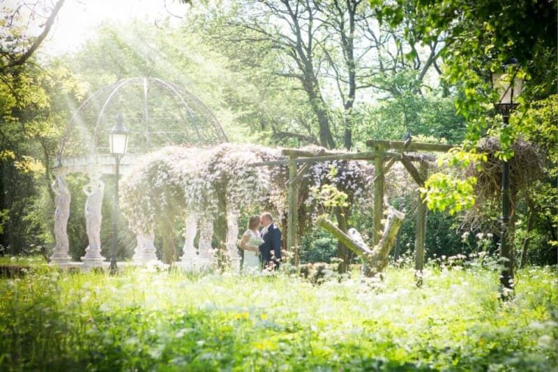Bride and groom kissing in the middle of a garden with sunshine coming down on them.