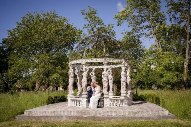 Bride and groom sitting under a marble gazebo-like structure with statues as columns.