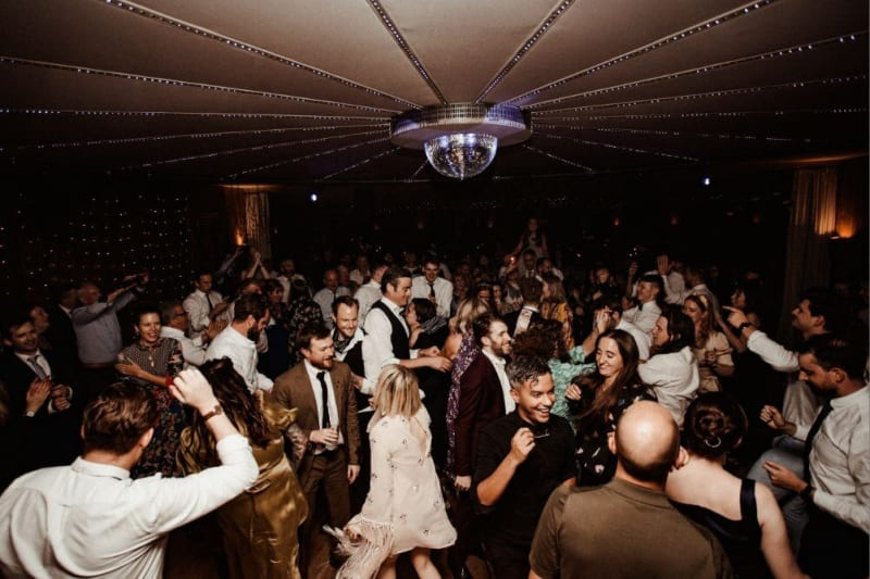 Lots of wedding guests dancing under a disco ball.