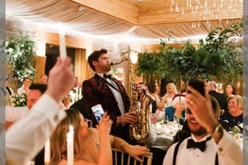 Man in tuxedo playing the saxophone at a wedding reception.