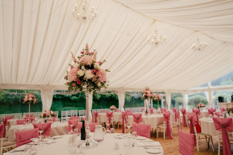 The interior of a tent decorated in white and pink.