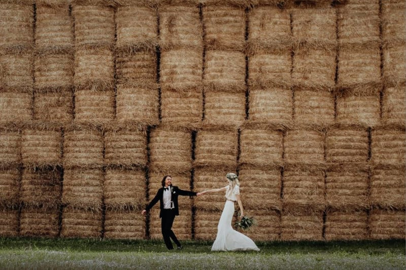 Bride and Groom hold hands. In the background, there are dozens of stacked piles of hay.