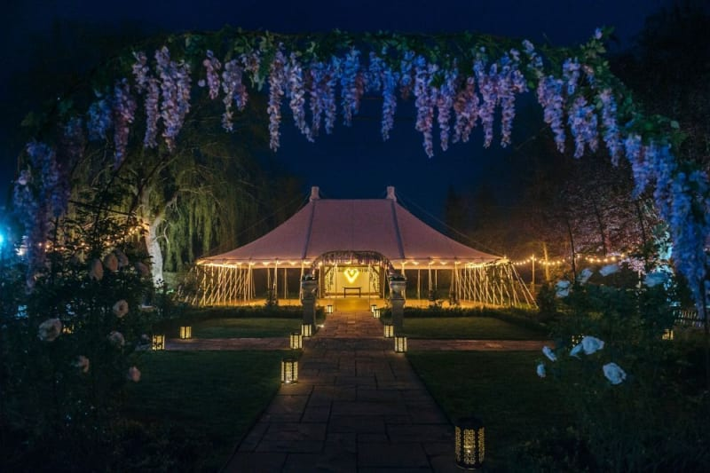 A white tent at night appears surrounded by lights. Purple flowers cover the frame.
