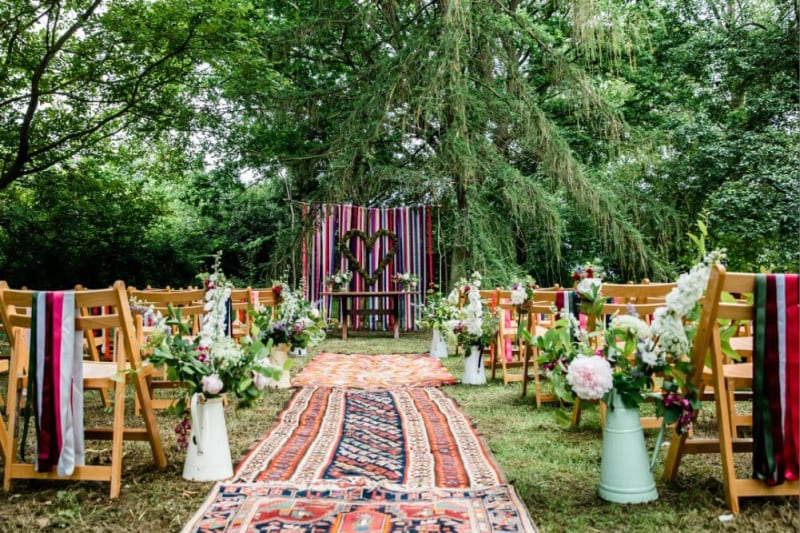 An outside ceremony is set with a festive and boho look.