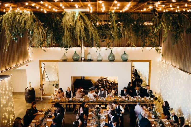 the reception room with four long wooden tables where people are seated. The room is covered in tiny lights.