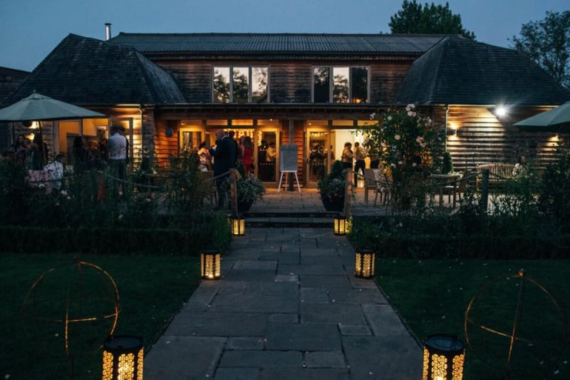 A wooden barn that also looks modern is filled with people.