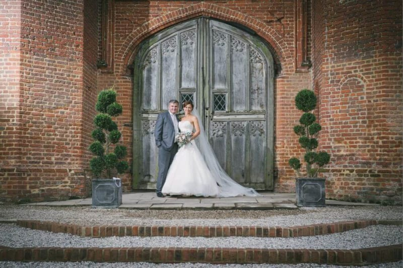 Bride and Groom stand in front of a big door filled with intricate details.