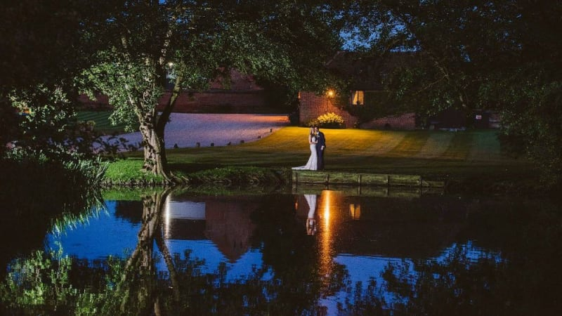 In the evening, the Bride and Groom stand beside a lake.