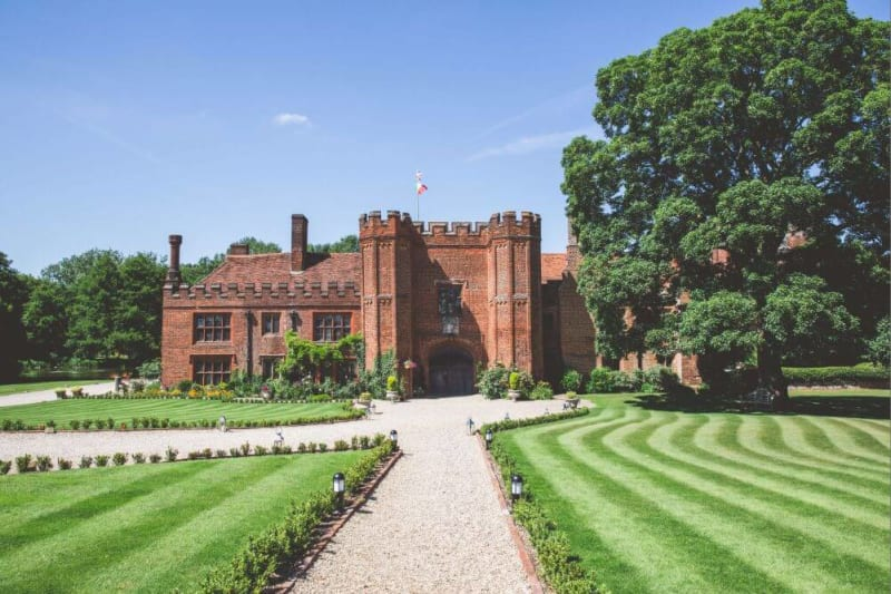 A brickhouse tudor style mansion is shown across well kept lawns.
