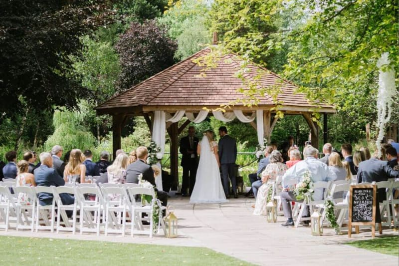 Wedding ceremony under a gazebo outside on a sunny day.