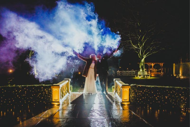 A newly wed bride and groom holding colourful smoke bombs in the air at night time.