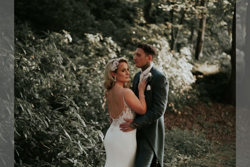 Bride and groom posing for a photo in the woods.