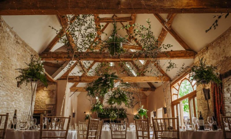 Inside of the venue, the oak beam ceiling is covered in plants.
