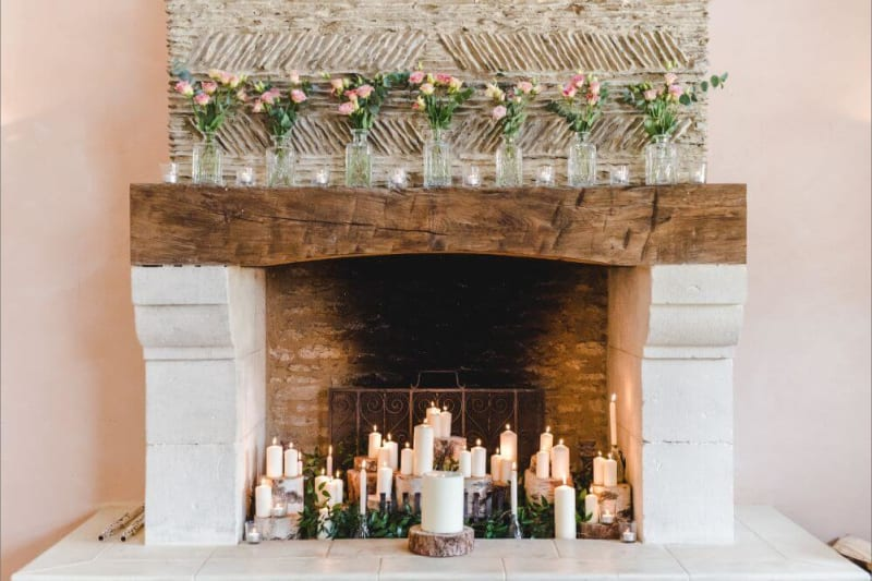 A variety of candles stands inside a white fireplace.