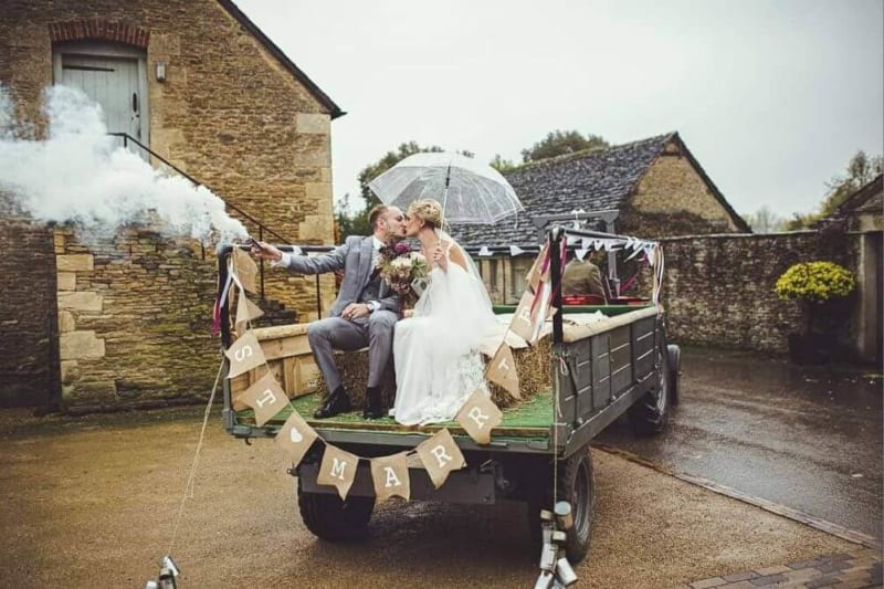 A couple rides the back of a carriage while kissing.