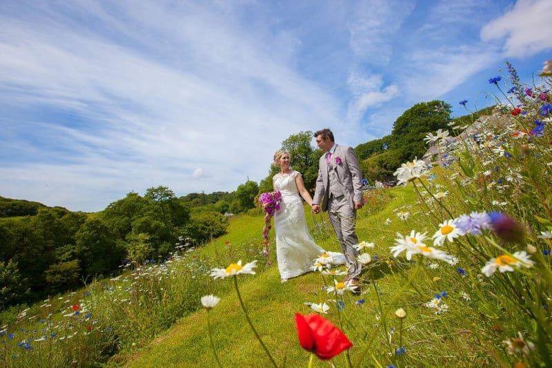 Bride and Groom take a stroll down a hill with flowers.