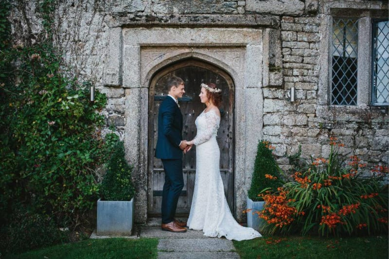 Bride and Groom look lovingly at each other in front of an ancient door.