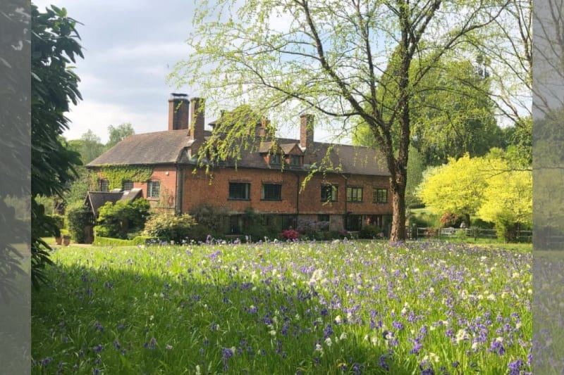 A brick house stands in a meadow filled with flowers and greenery.