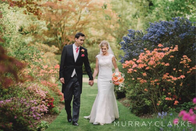 Bride and Groom hold hands and walk past the flowers.