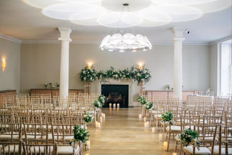 Chairs and aisle set up and decorated with flowers inside for a wedding ceremony.