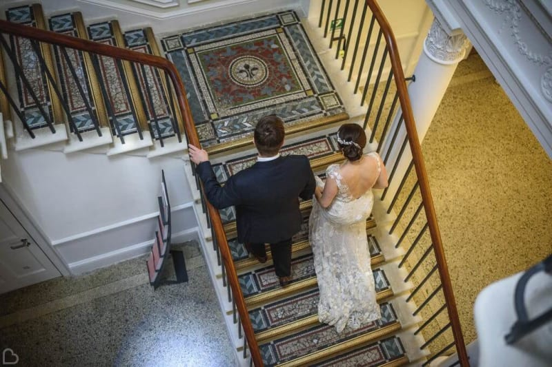 Bride and groom walking up a staircase.