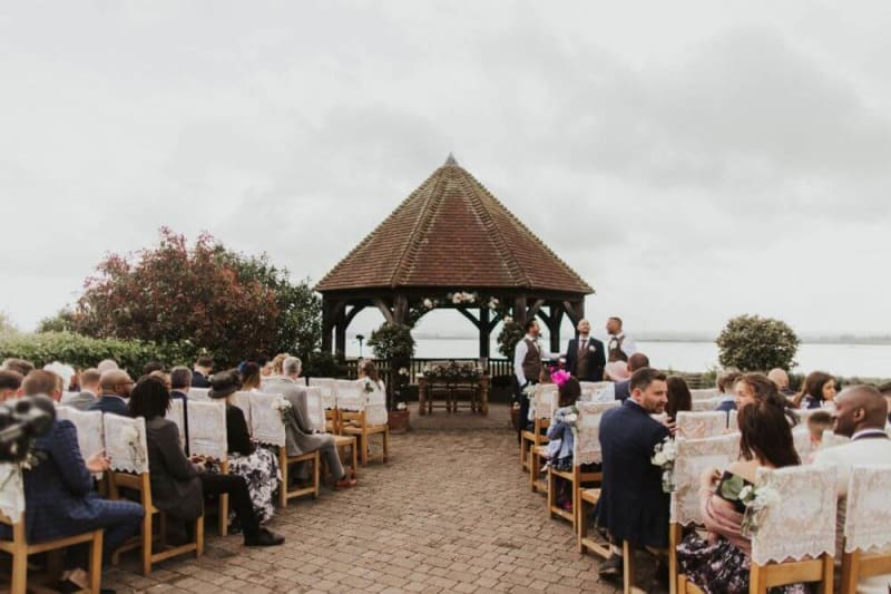 The Brown Gazebo in the garden surrounded by chairs filled with people waiting.