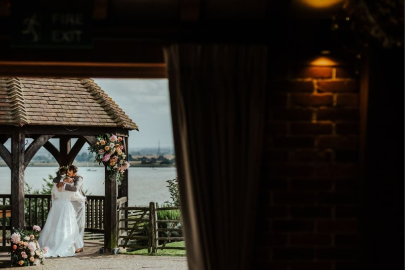 The bride and groom embracing outside under the wooden gazebo.