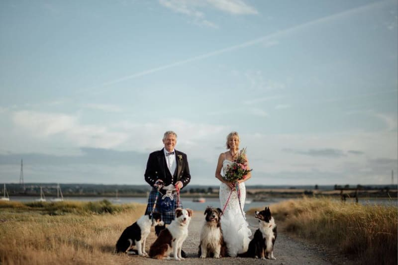 Bride and Groom stand with 4 dogs smiling.