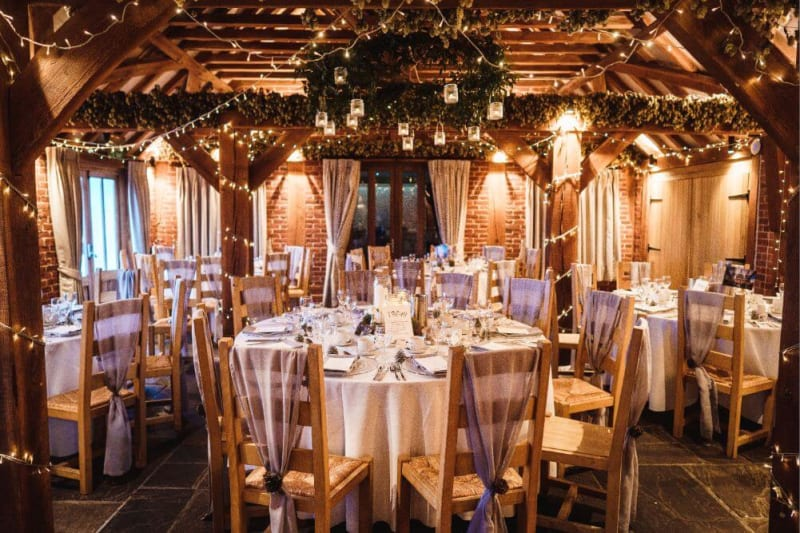 Inside shot of the reception room filled with wooden tables and chairs with lights adorning the beams.